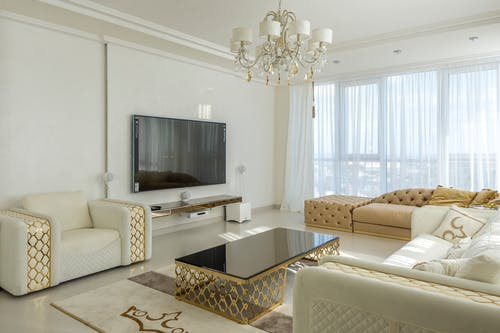 White and beige interior of modern comfortable living room with big sofas and armchair