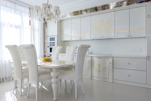 Light kitchen interior with white furniture with golden print dining table and chairs in classic style