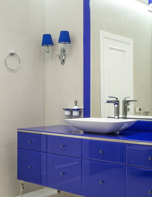 Interior of modern bathroom with blue cabinet with mirror and vessel sink and sconce on wall