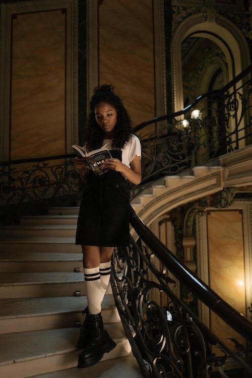 階段の上に立っている黒いドレスの女性