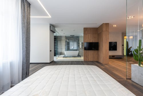 Interior of modern spacious apartment with wooden floor glass walls and bedroom looking into bathroom