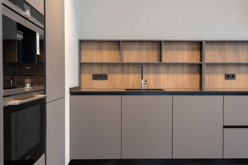 Modern kitchen interior in minimalistic style with grey furniture and built in appliances