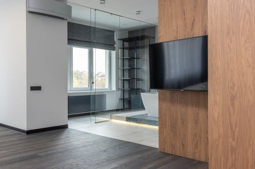 Modern unfurnished apartment with TV on wooden wall and bathroom with glass doors