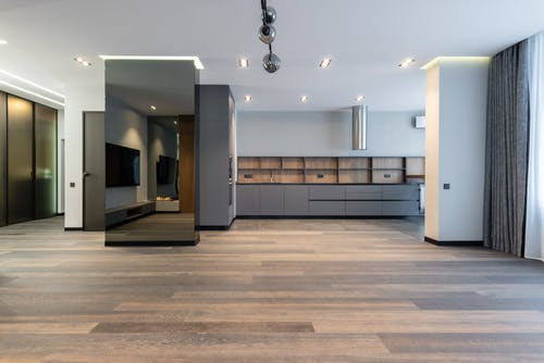 Modern unfurnished apartment with free space looking into dining area and mirrored pillar