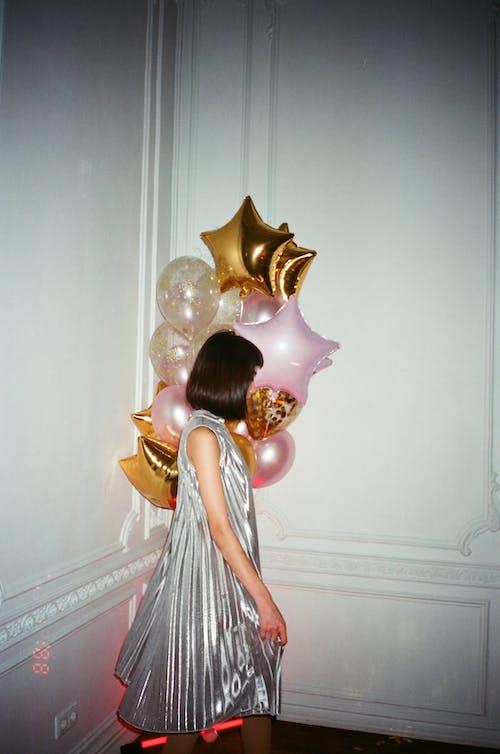 金の風船を保持している白いドレスの女性