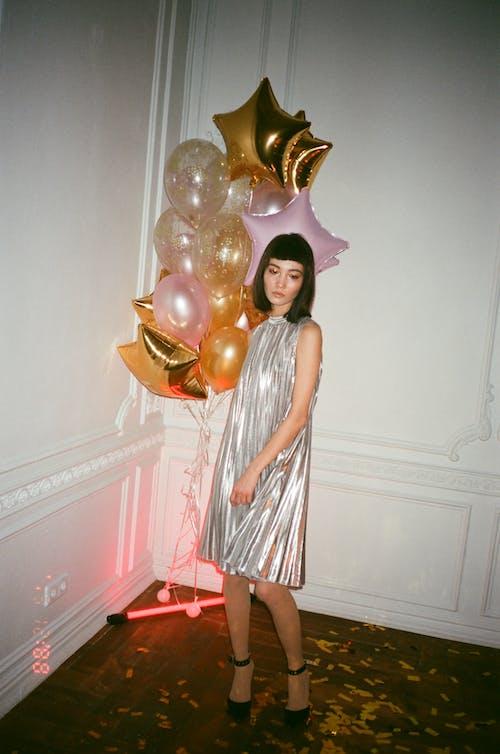 白い木製のドアの横に立っている灰色と白のストライプのノースリーブドレスの女性