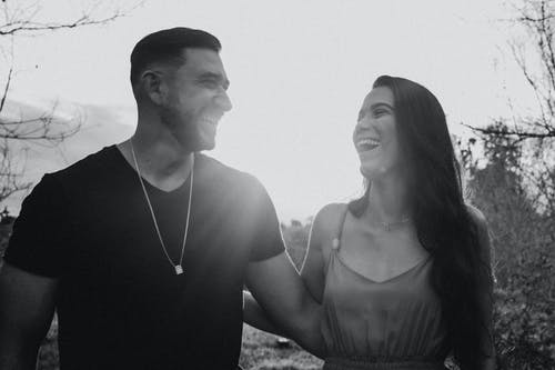 Black and white of young happy Hispanic couple embracing while talking and looking at each other in sunshine