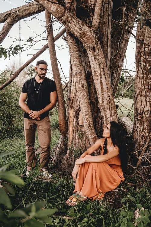 Elegant Hispanic woman resting near tree and masculine boyfriend