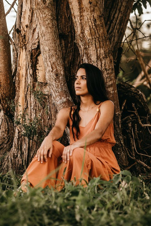 Dreamy Hispanic woman resting near tree in countryside