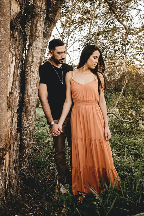 Dreamy Hispanic couple holding hands near tree in countryside