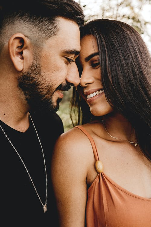 Crop bearded Hispanic man with charming girlfriend looking at each other while spending time together