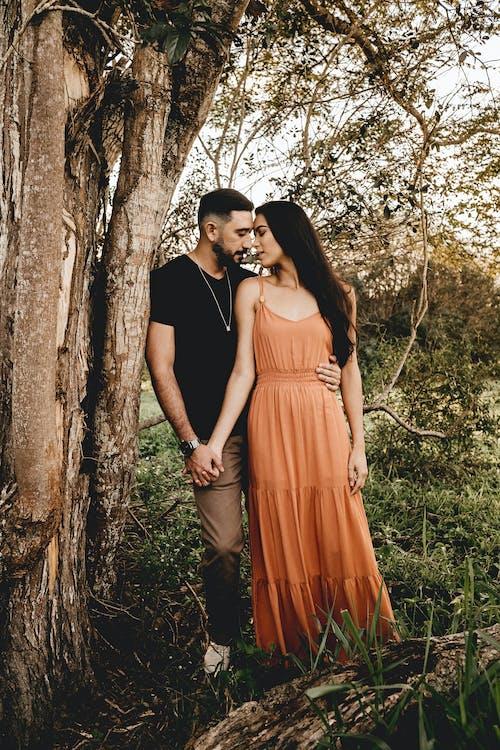 Hispanic couple embracing near tree in countryside