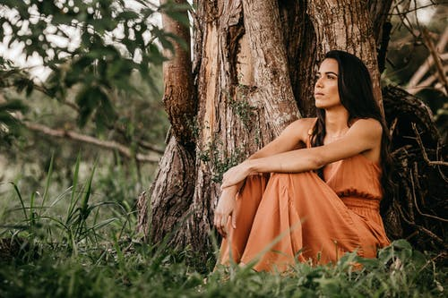 Young serene Hispanic female in elegant clothes looking away while resting near massive tree in daytime
