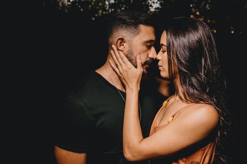 Side view of young tender Hispanic female embracing bearded male partner while looking at each other