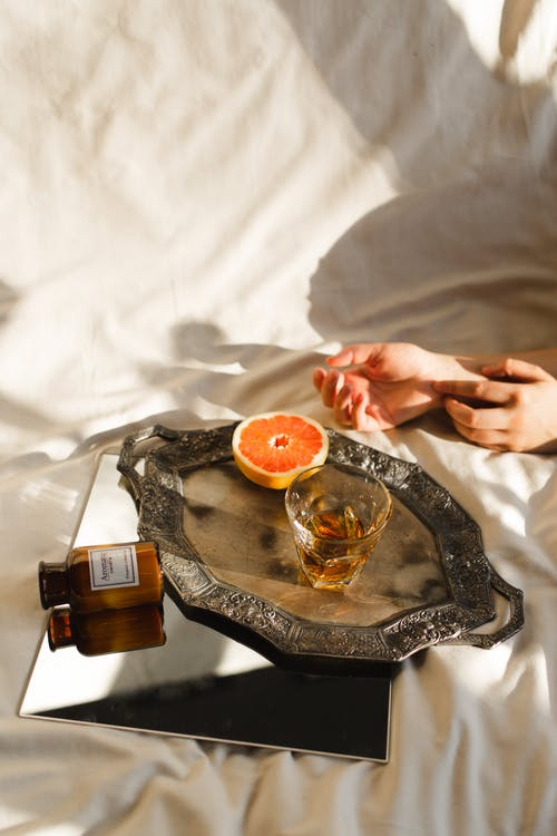 From above of crop anonymous female resting on crumpled bed sheet with ripe orange and alcoholic drink in glass on tray