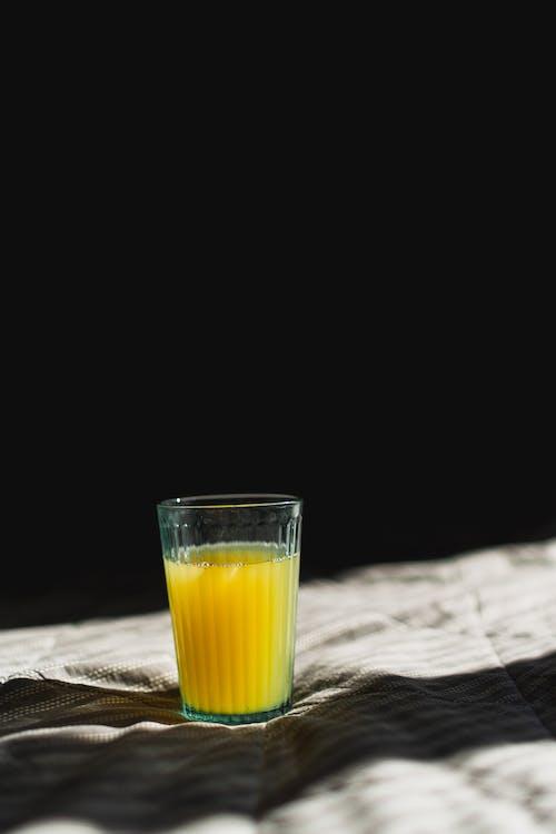 Glass of fresh orange juice on fabric with shadow