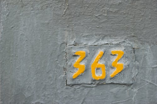 Painted yellow numbers 363 on cracked gray wall
