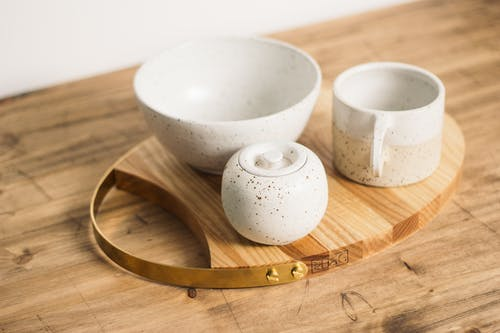 From above stylish minimalistic tea set of light ceramic in dark spots served on oval wooden board