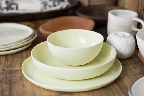Set of stylish light ceramic crockery including bowls tea cups and plates placed on wooden table