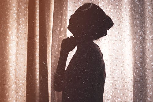 Side view silhouette of anonymous female standing in room near curtains in sunlight