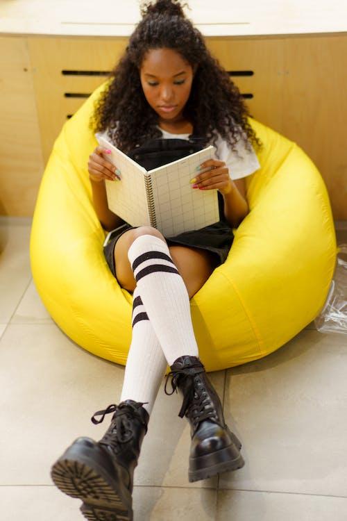 黄色い椅子に座っている黒い革のブーツの女性