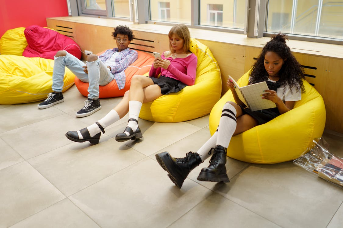 Group of Women Sitting on Yellow Couch