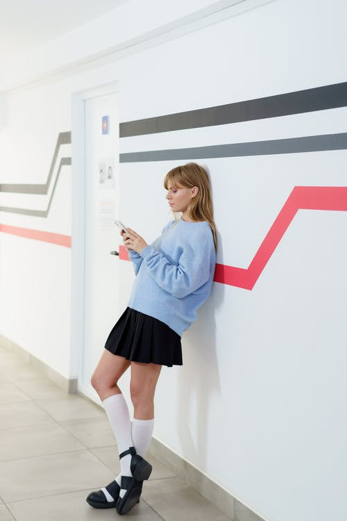 Pretty Woman Leaning on a Wall while Using a Cellphone
