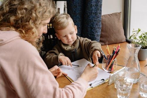 A Woman Teaching a Boy to Draw