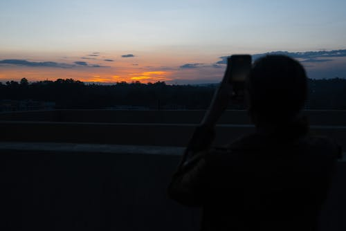 Person Taking Photo of Sunset