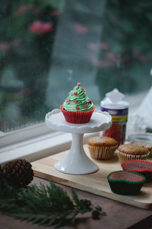 Tasty cupcake with green frosting topped with sprinkles placed on stand with muffins on windowsill near window with coniferous branch