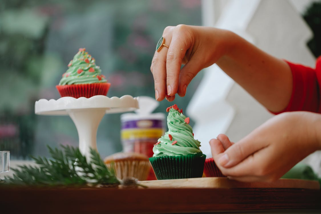 Unrecognizable female sprinkling topping on green frosting of cupcake while standing near windowsill with wooden board and coniferous branch on blurred background