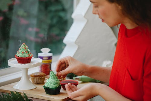 Side view of female cook putting sprinkles on frosting of cupcake while standing near window during holiday preparation at home