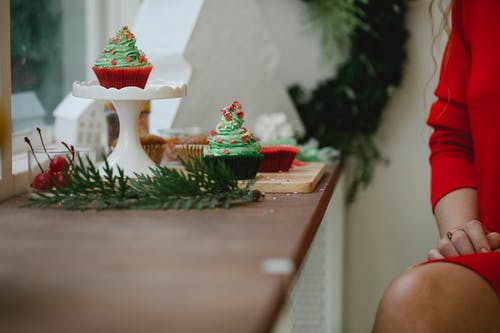 Crop anonymous female in red dress sitting at windowsill with Christmas composition with fir tree branch and colorful cupcakes at daytime