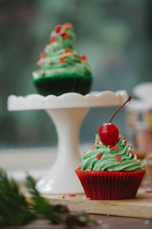 Sweet cupcake with red cherry on table