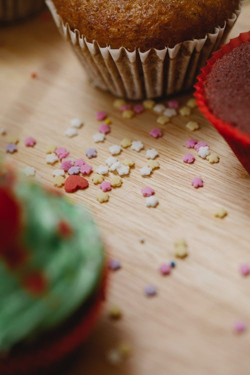 High angle of colourful sugar stars sprinkles for cakes and cupcakes in cases on wooden table