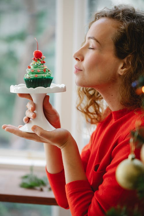 Side view of young woman with closed eyes holding plastic stand with cupcake decorated with red cherry