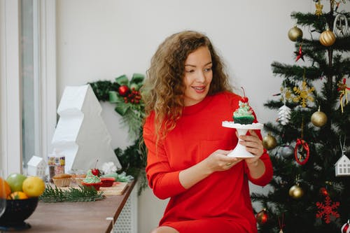 Cheerful young woman holding stand with cupcake sitting beside decorated fir tree at home