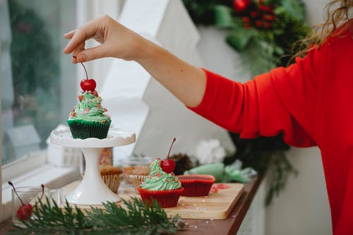 Woman making Christmas cupcakes with berries