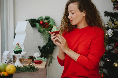 Happy young woman enjoying fresh delicious cupcake with green whipped cream standing beside decorated Christmas fir tree