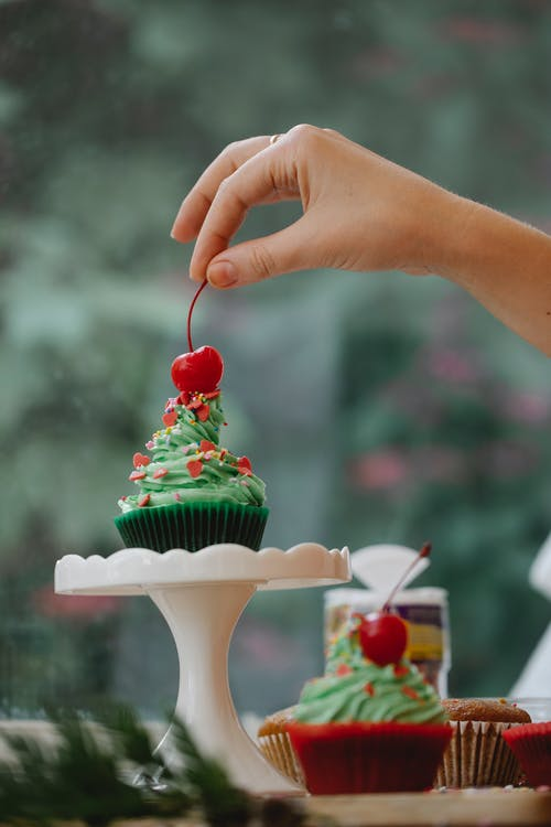 Unrecognizable woman putting red cherry on top of Christmas muffin on stand preparing for festive party
