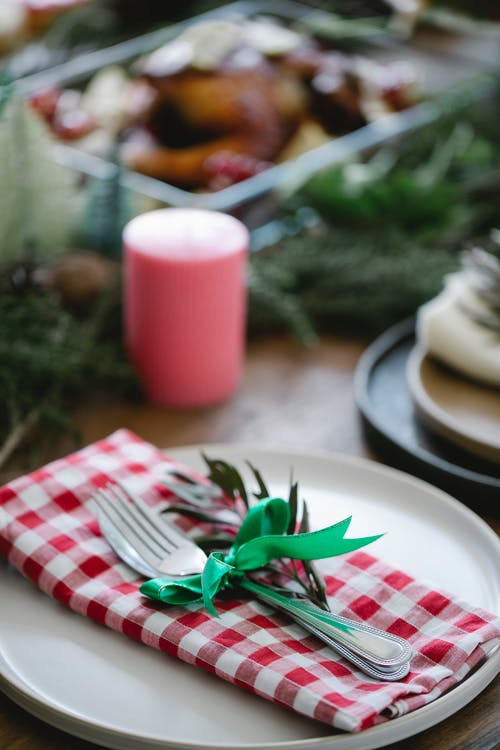 Table served for Christmas dinner with rustic checkered napkin and decorated with fir twigs