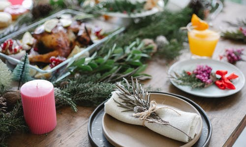 High angle of table served for Christmas dinner with plates with napkins and traditional roasted turkey on glass dish decorated with fir twigs