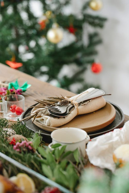 Served table with dishware and cutlery near fir sprigs during Christmas holiday in house