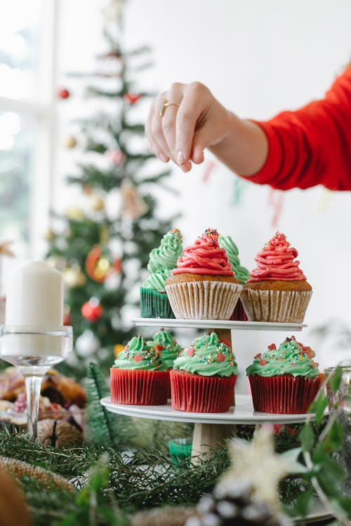 Crop anonymous female chef decorating appetizing cupcakes with buttercream on top during New Year holiday in house
