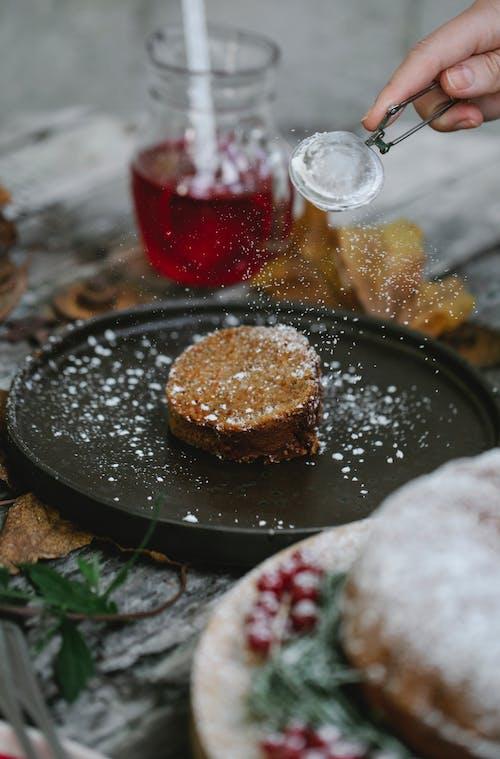 Crop unrecognizable chef garnishing pie slice with sugar powder