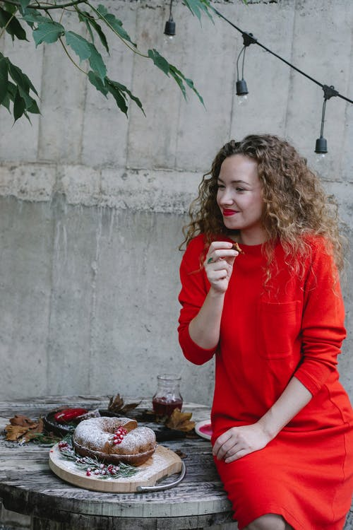 Content young female wearing red dress enjoying sweet fresh pie and sitting on round wooden table on backyard