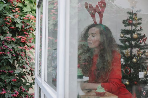 Through window of thoughtful woman with long curly hair in bright outfit near window in festive room with Christmas tree and looking away in daytime