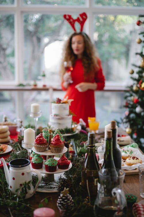 Woman with wine glass standing near Christmas tree and decorated table