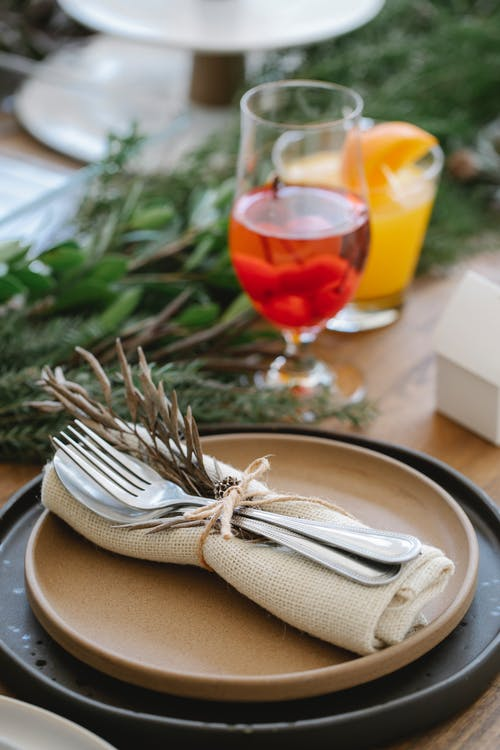 High angle of served table for Christmas dinner with plates and glasses decorated with coniferous twigs