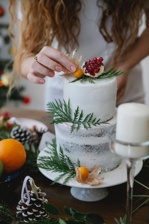 Crop anonymous female decorating homemade cake with fresh berries and herbs placed on table in exquisite plate for Christmas celebration